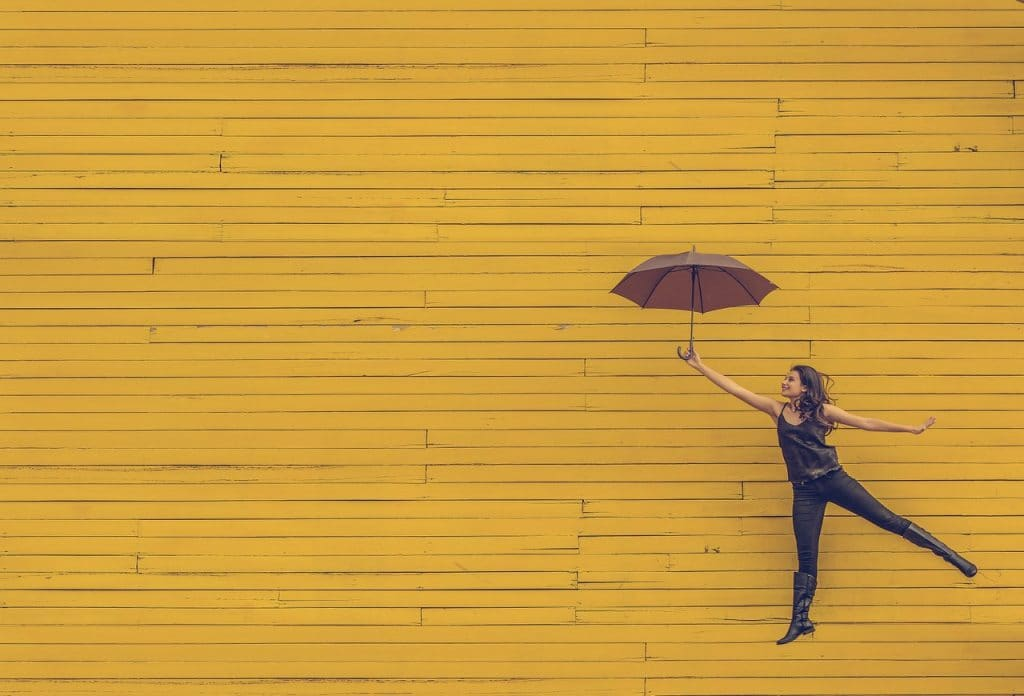 Woman holding an umbrella in front of yellow wall