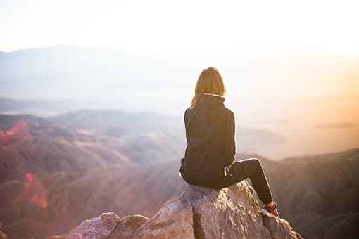 woman sitting on a cliff looking at the sun love yourself first quotes