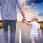 dad holding child's hand walking down the road