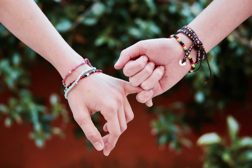 two hands holding by their pinkies friendship quotes