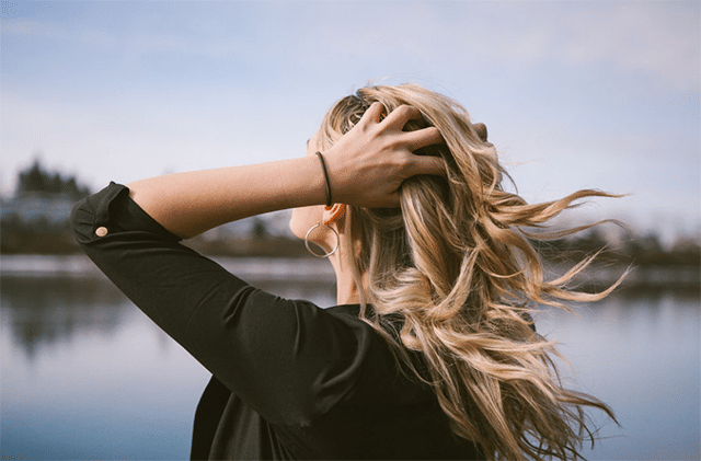 Woman touching her blonde hair as she reflects on some anger quotes