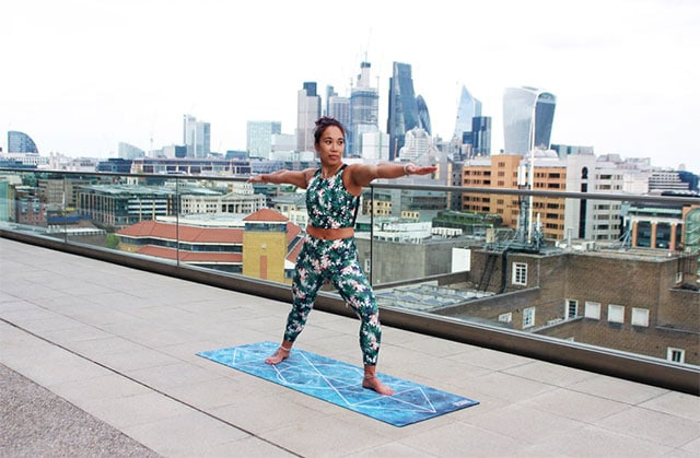 woman doing yoga outdoors on a rooftop
