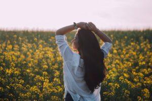 a woman standing near a flower field