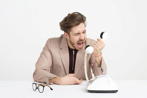 man shouting at telephone